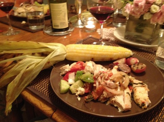 Greek dinner plate with Santorini grilled chicken, Greek salad, corn, and red wine.
