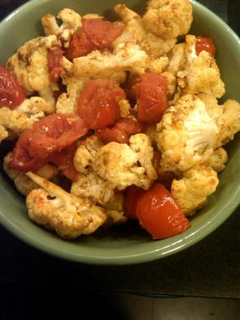 Roasted cauliflower with cumin and tomatoes in a green bowl.