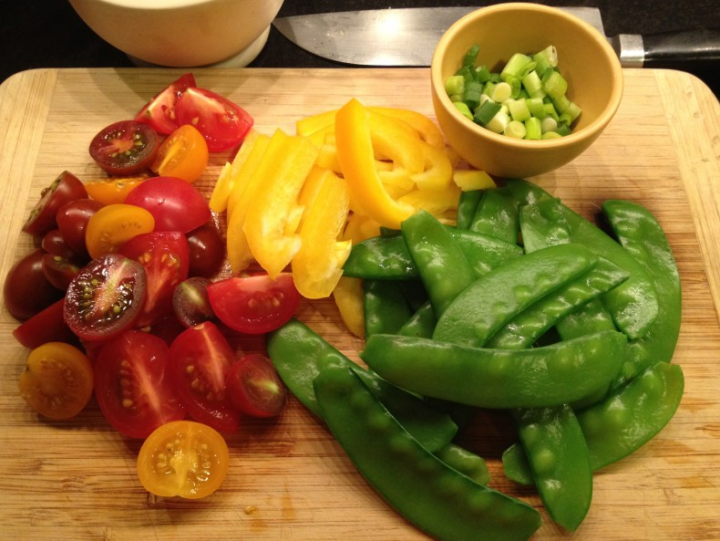 Sirloin steak salad ingredients including snow peas, yellow pepper, scallions, and cherry or grape heirloom tomatoes on a wooden cutting board.