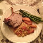 Crown roast of pork with sauteed apples, Italian beans, and roasted asparagus on an antique Wedgewood plate on a beautiful tablecloth
