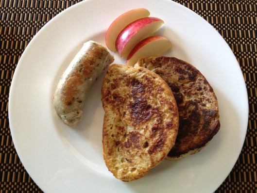 A breakfast of turkey sausage, French toast and sliced apples on a white Wedgewood plate.