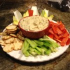 Bean dip in a red bowl with vegetables and crackers.