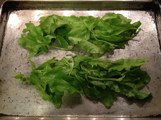 Piles of sorrel on a baking sheet, drizzled with olive oil and seasoned with salt and pepper.