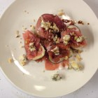 Figs wrapped with proscuitto topped with Stilton, toasted walnuts, olive oil and balsamic vinegar on a white plate.