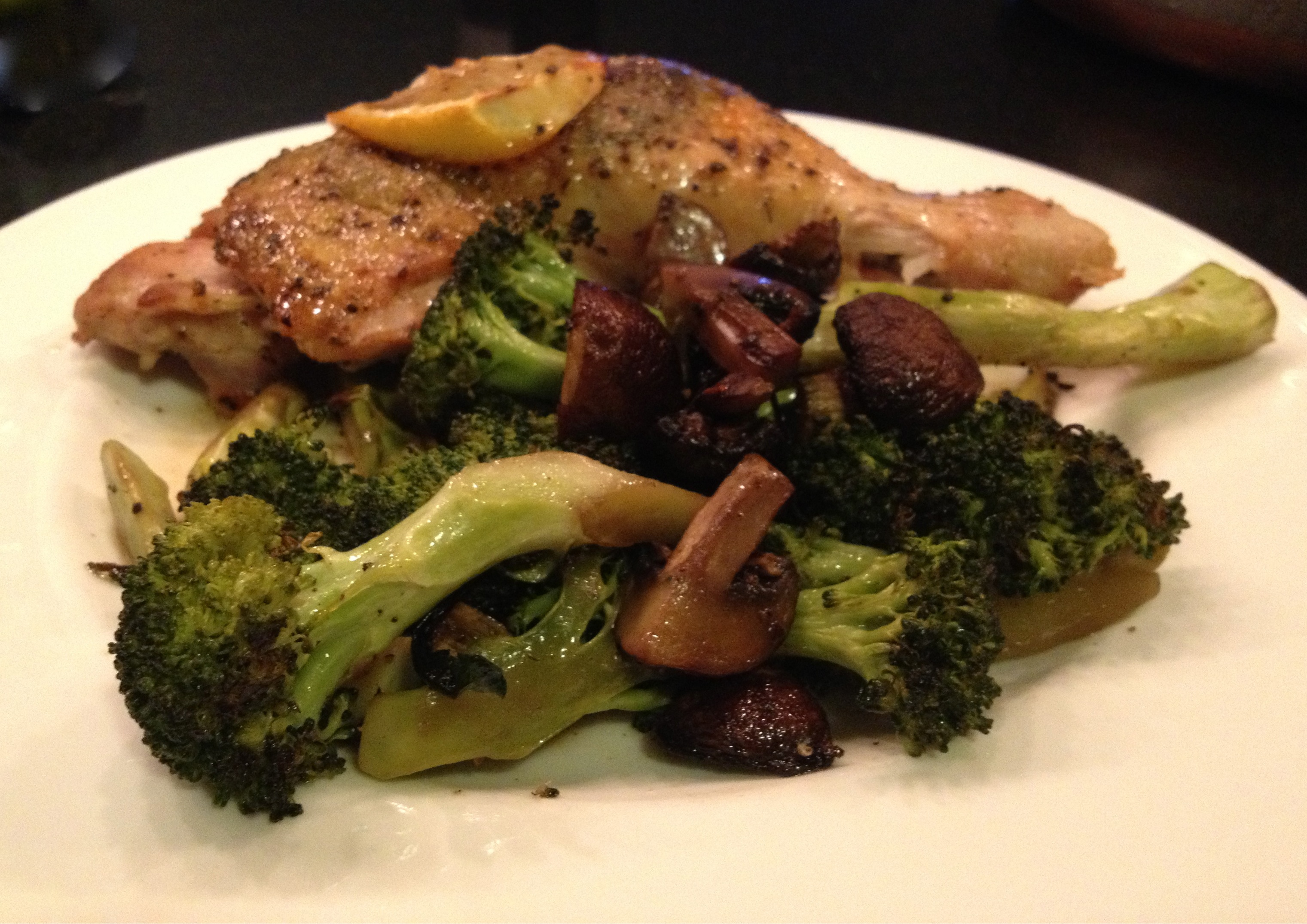 Provencial roast chicken legs with oven roasted broccoli and mushrooms on a white Wedgewood plate.
