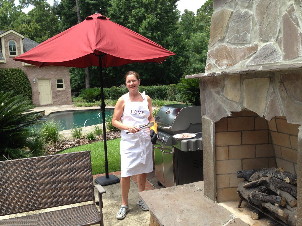 Nikki Landau in a LOVE apron outside her home in Alabama with a large stone fireplace and pool in the background.