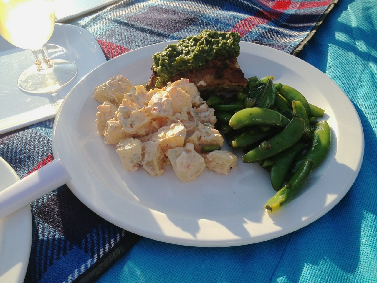 Roasted chicken with chimichurri sauce, potato salad and sugar snap pea salad on a white plate.