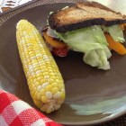 Bacon, lettuce and tomato sandwiches with an ear of corn on a brown plate.