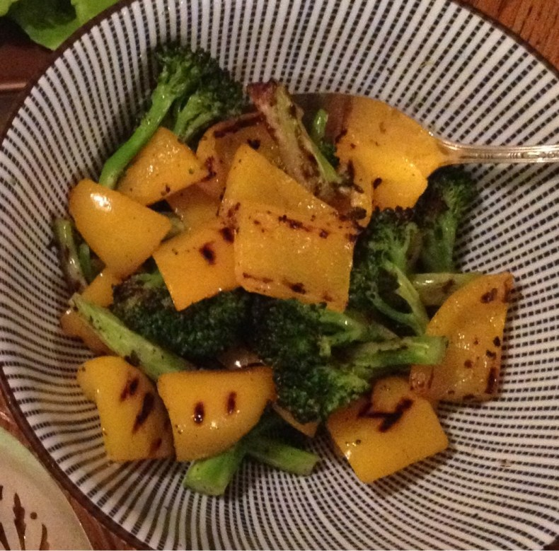 Grilled broccoli and yellow peppers in a blue and white striped bowl..