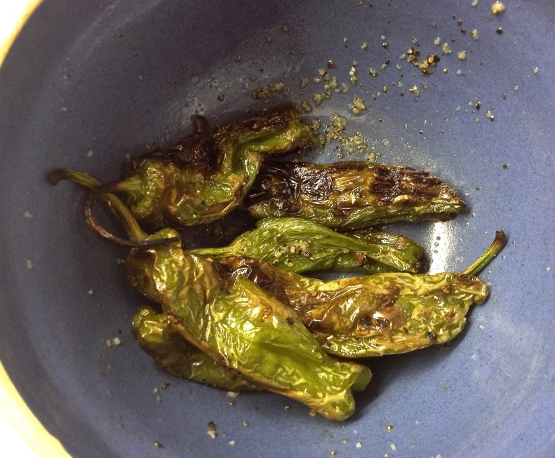 Grilled shisido peppers in an antique blue pottery bowl.