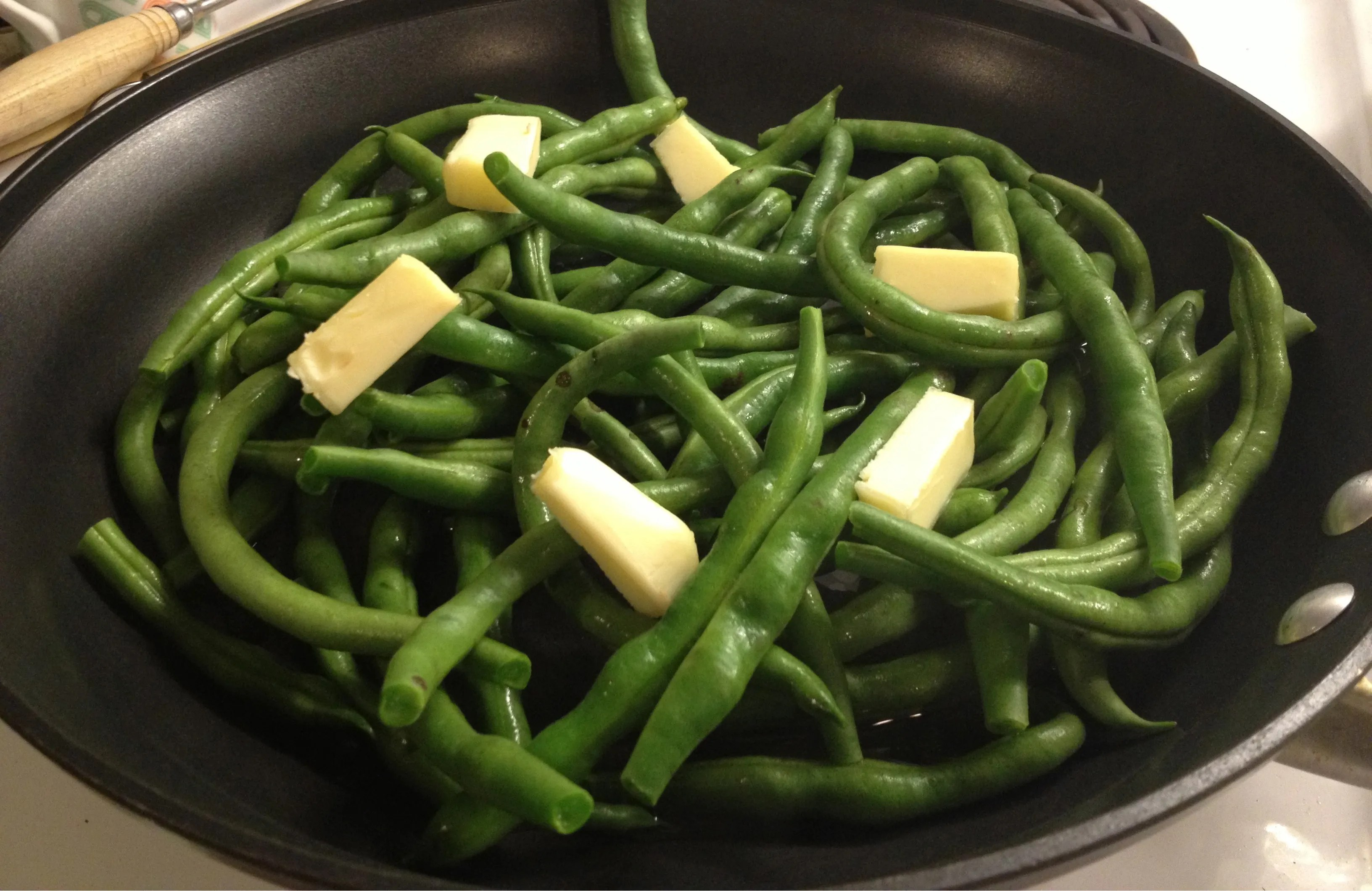 Green bean recipe with farm fresh beans, in a skillet with butter, ready to be cooked.