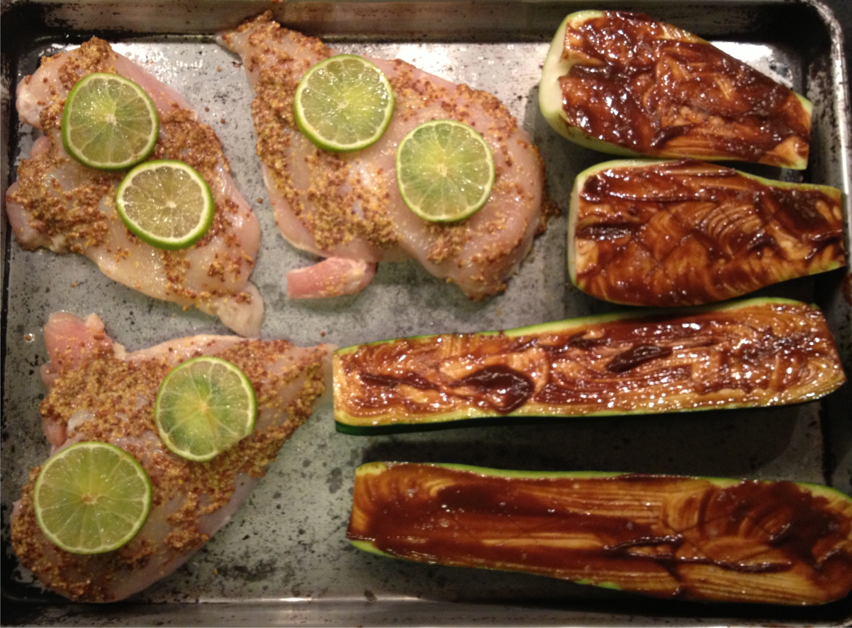 Tarmarind squash and raw mustard-coated chicken breasts with jalapeno and lime slices on a baking sheet.