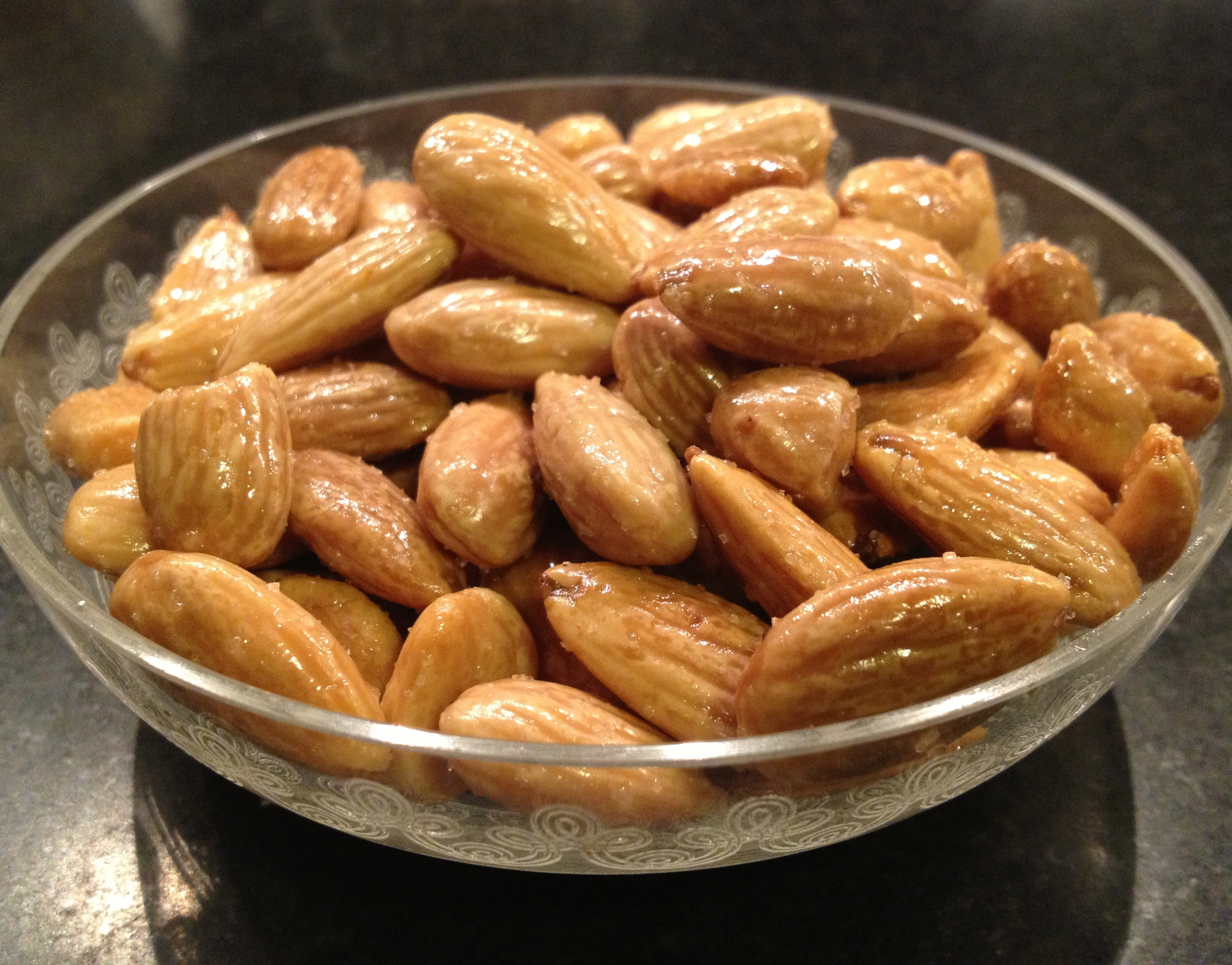 Roasted almonds in a glass crystal bowl.