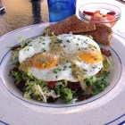 sunny side up eggs on a bed of frisee with crispy bacon topped with a tomatillo sauce