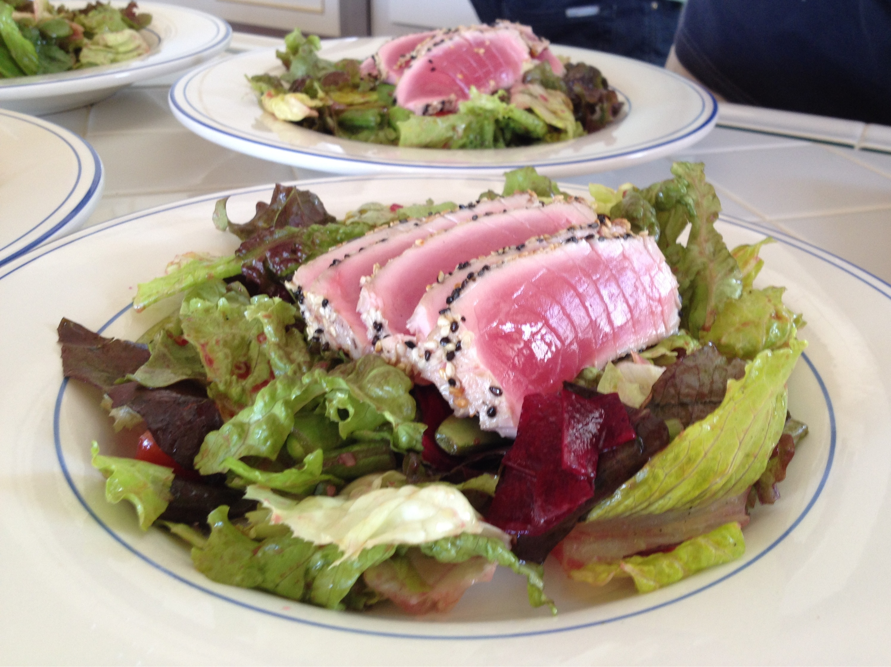 seared sesame crusted tuna on a bed of lettuce with raw beets and sugar snap peas