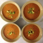 Four bowls of golden gazpacho garnished with diced avocado.