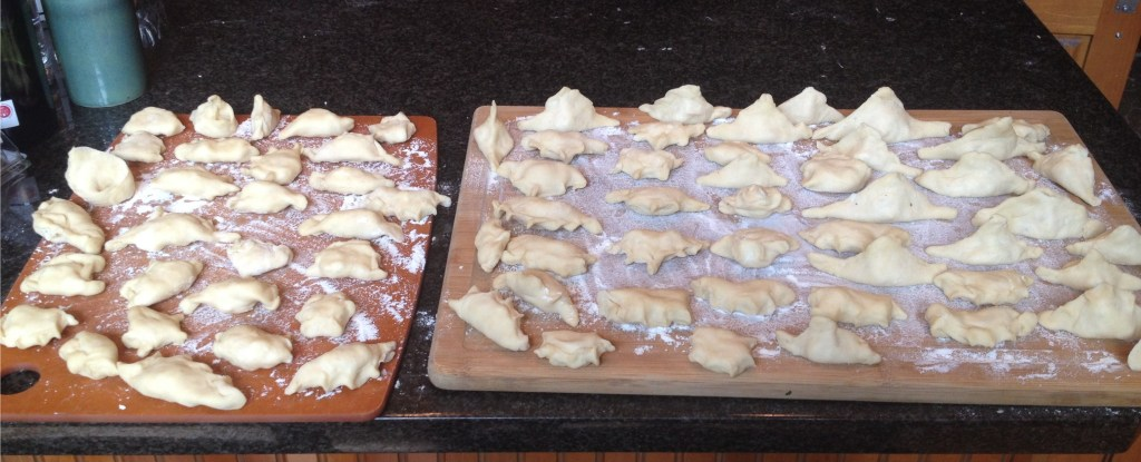 Pierogi ready to cook on wooden boards.