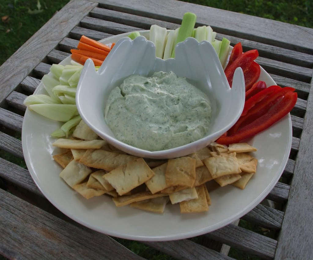 Spinach mix dip in a bowl with crudites and crackers.
