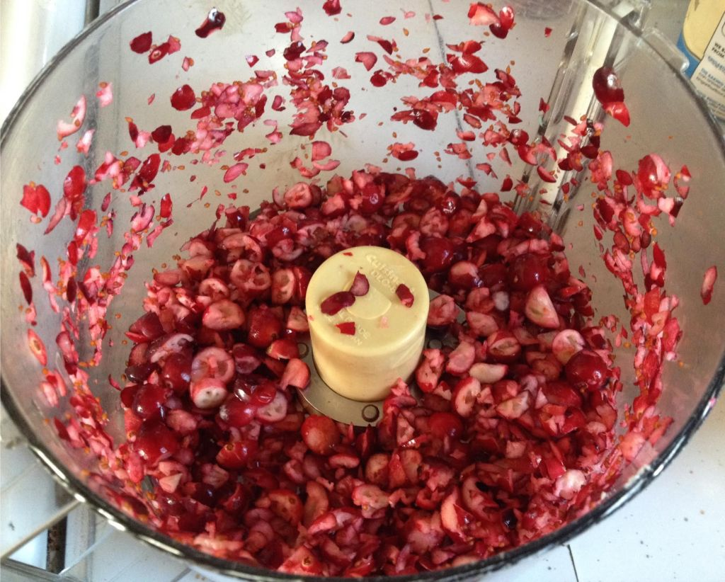 Chopped fresh cranberries in a food processor bowl.