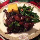Duck braised with red wine and prunes on a plate.