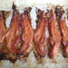 Cooked bacon on a parchment lined sheet.