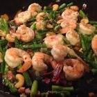 Shrimp and asparagus stir fry in a skillet.