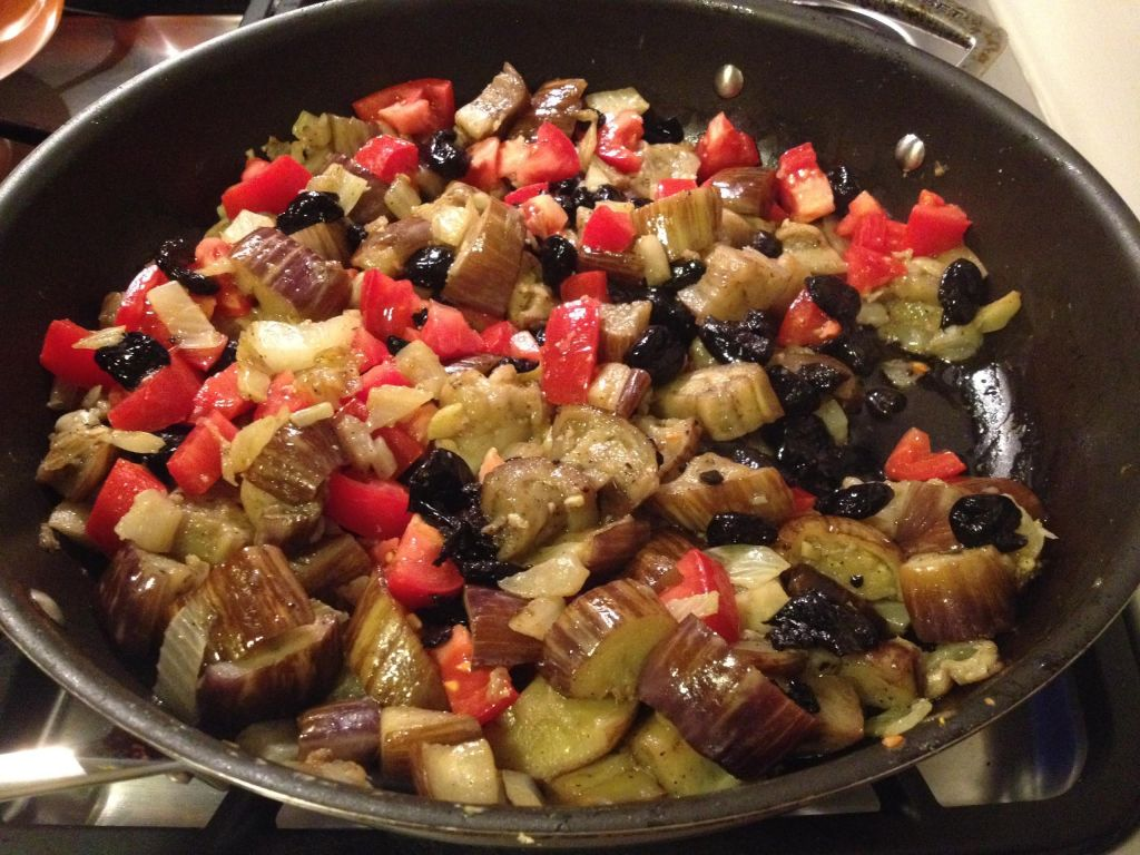 Eggplant, mozzarella and oil cured black olives in a skillet.