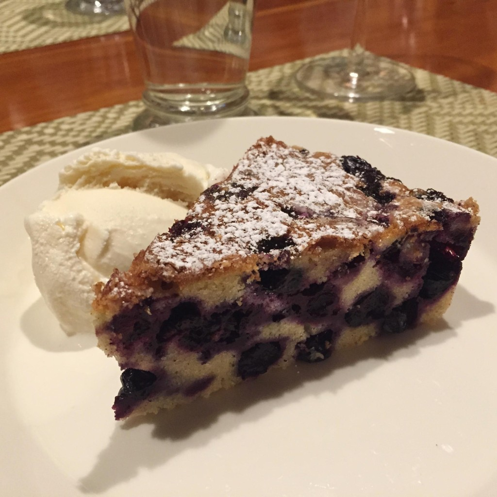 Blueberry buckle piece with ice cream on a white plate.