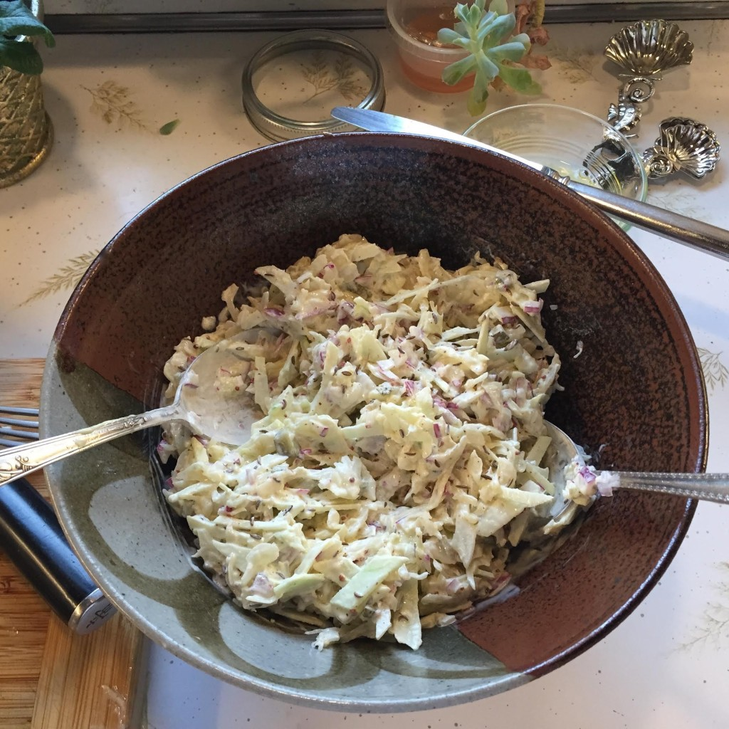 Sauerkraut salad with string cheese in a bowl before garnishes.