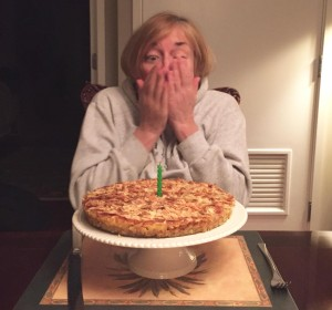 Mary finished blowing out the candle on a pear almond tart.