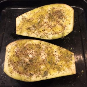 Seasoned raw eggplant halves, scored.