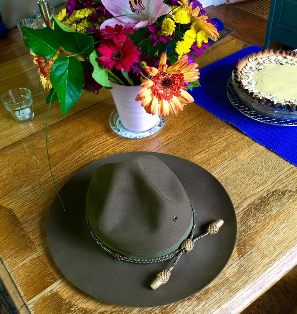 WWII cavalry hat with flowers and pie in the background.