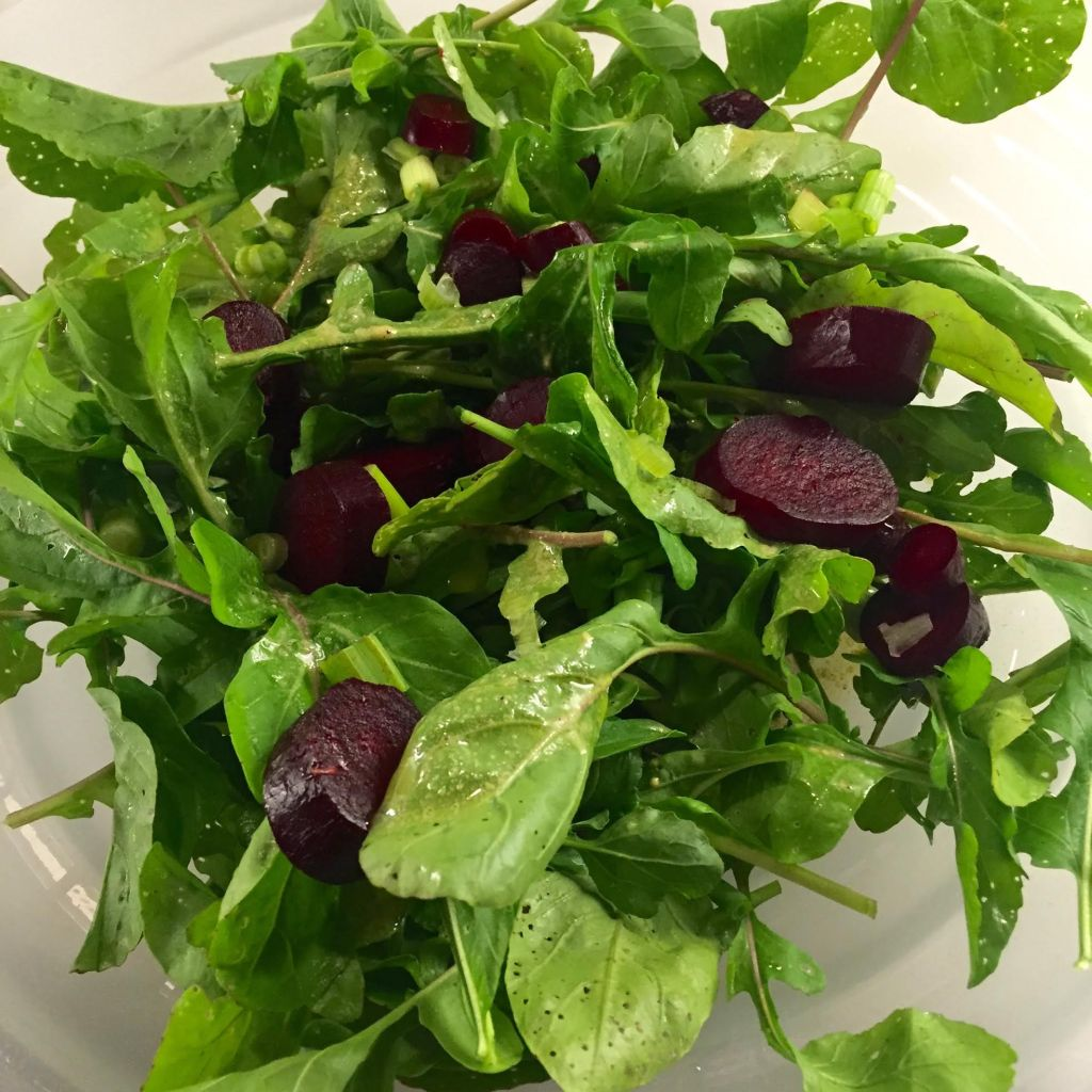 Arugula, roasted beet and scallion salad in a bowl.