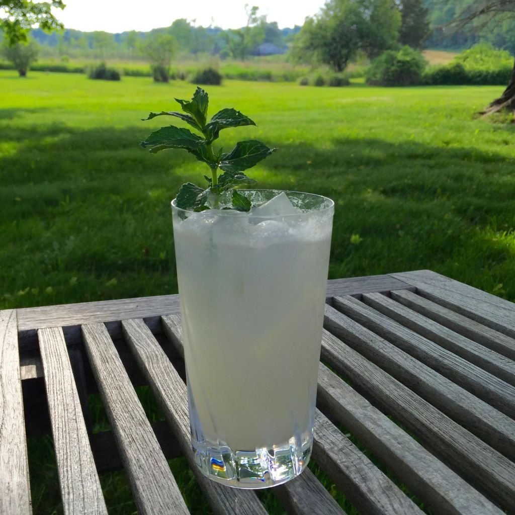 Frosty cocktail on a teak table outdoors.