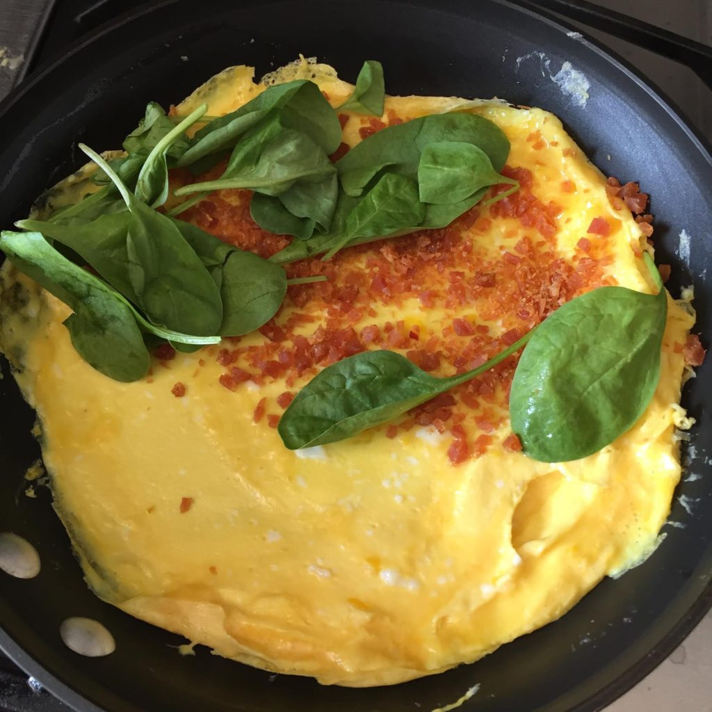Chef's Cut Honey Barbeque Chicken Jerky & Spinach Omelet in a pan.