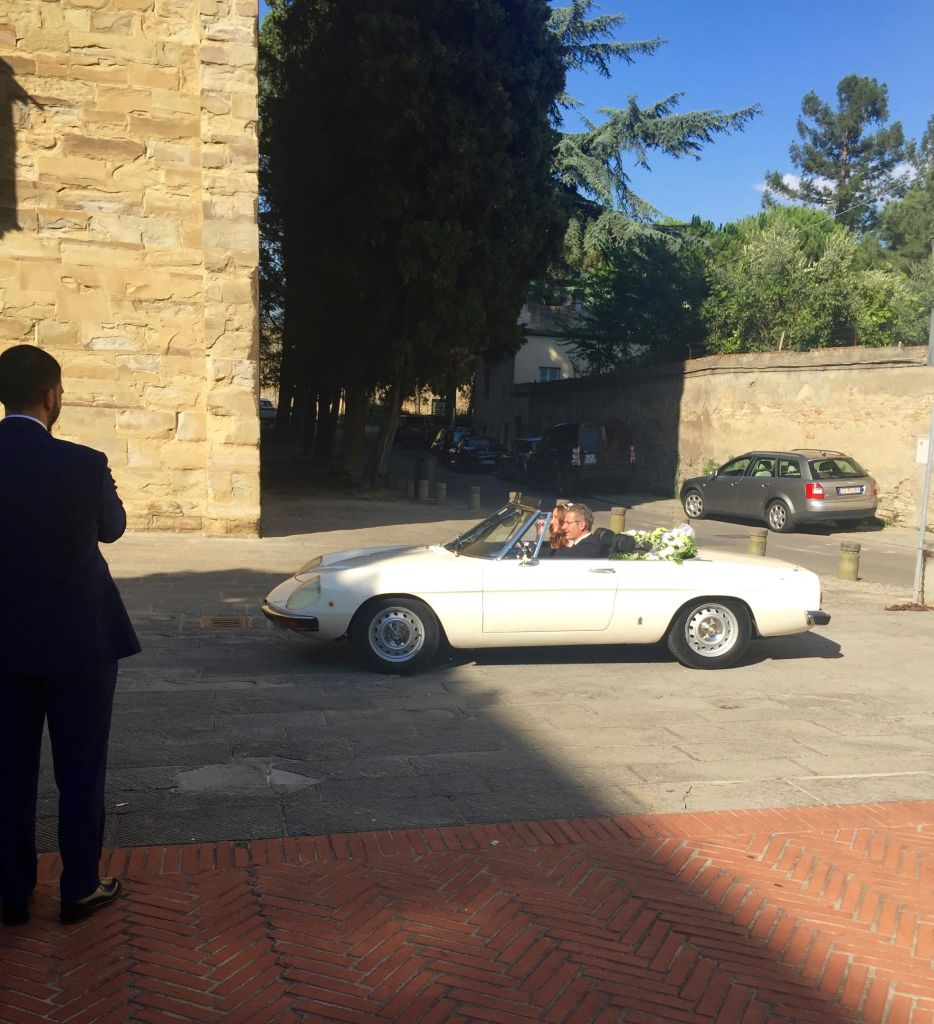White convertible Alfa Romeo car with a bride and her father.