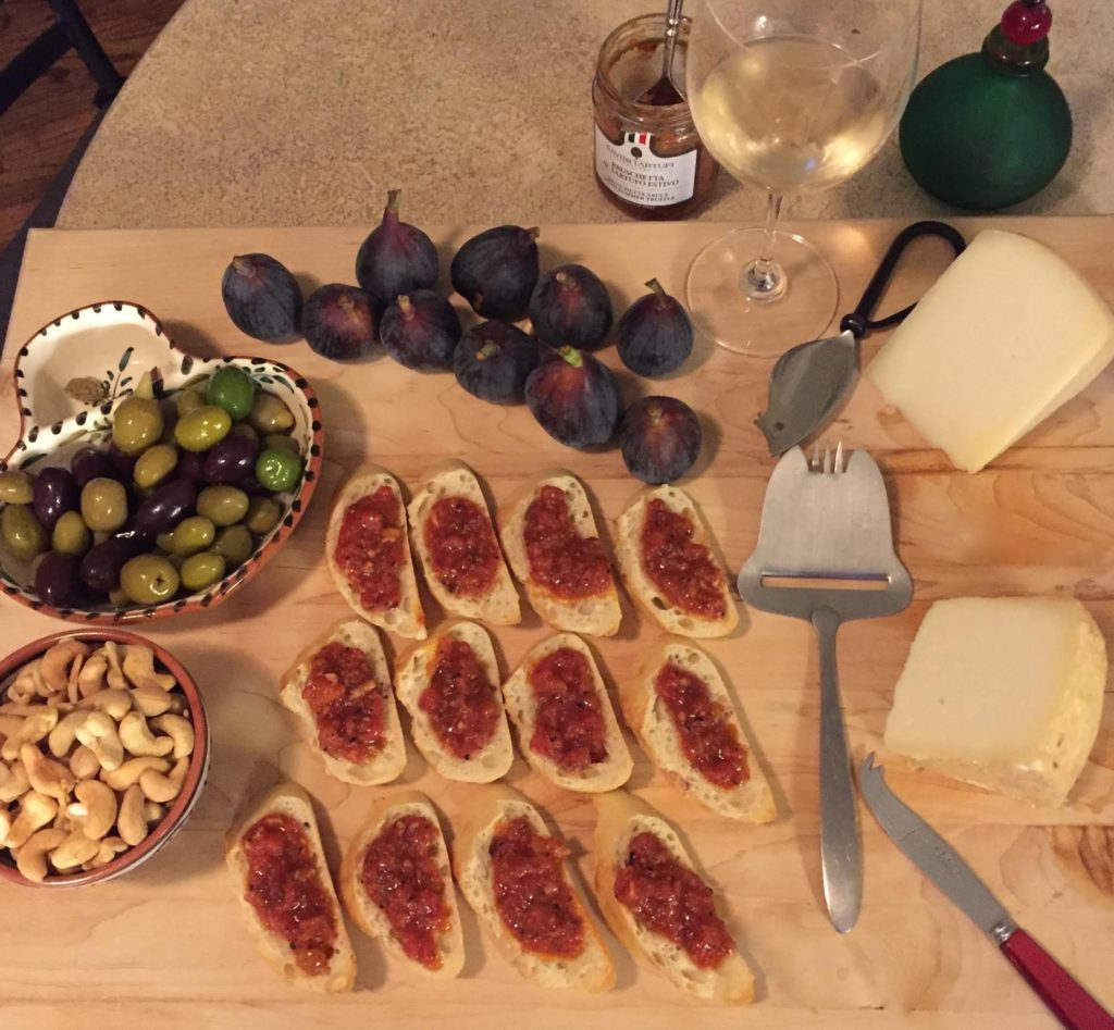 Bruschetta‎, olives, fresh figs, cashews, and 2 kinds of Pecorino on a wooden board with a glass of white wine.