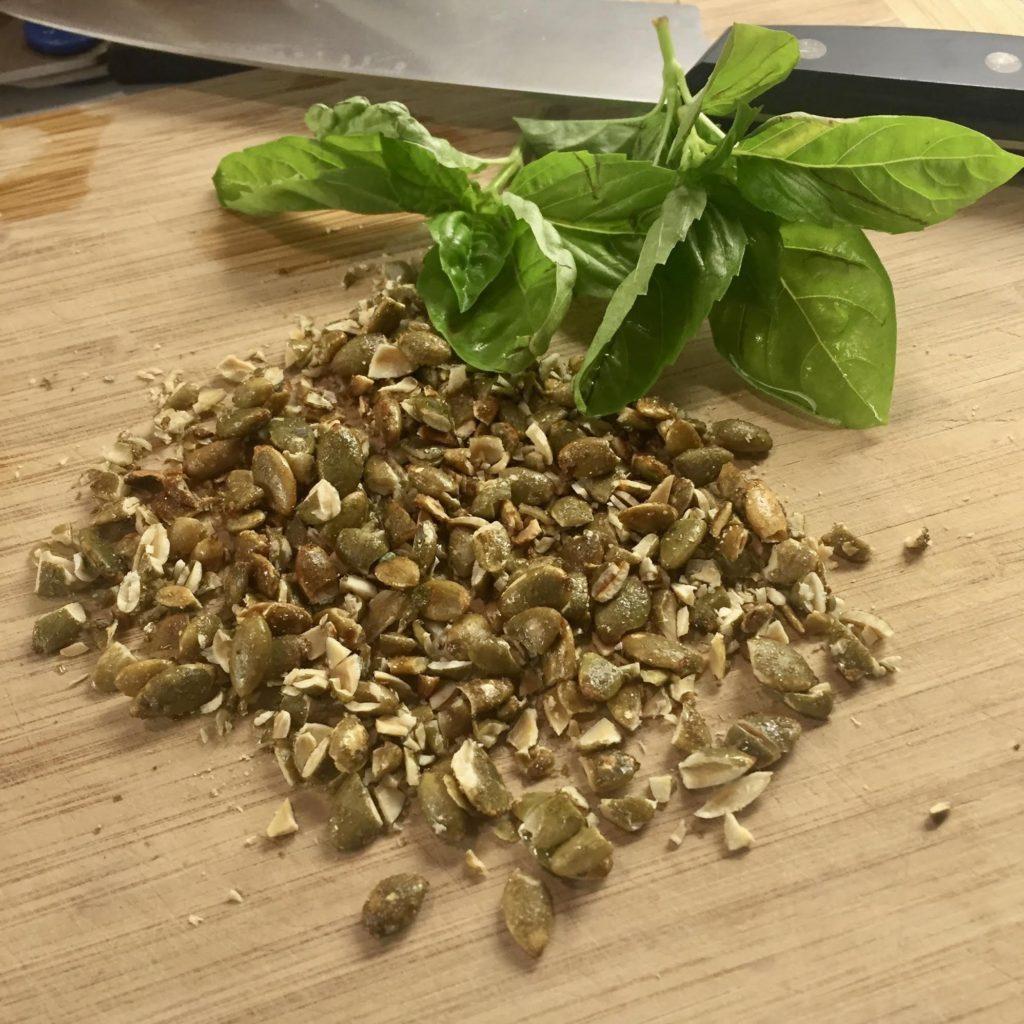 Chopped Maple Sugar & Sea Salt Superseedz with fresh basil leaves on a wooden cutting board.