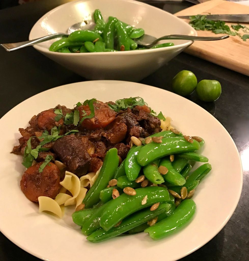 Lamb stew over egg noodles with blanched sugar snap peas topped with pepitos in a white bowl.
