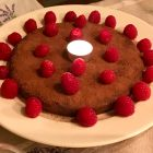 Jean-Georges chocolate cake garnished with fresh raspberries and a tea light.