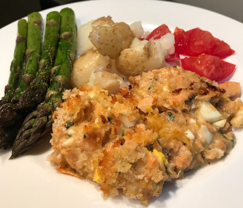 Salmon casserole plated with asparagus, boiled potatoes, and tomatoes.