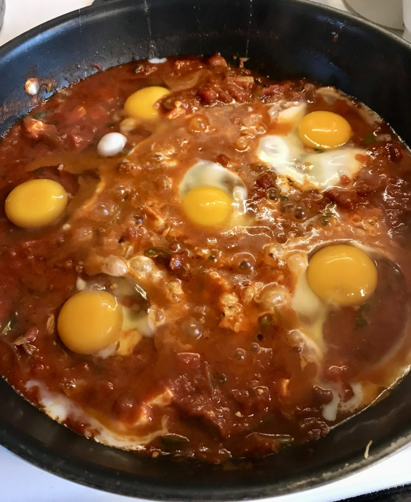 Shakshuka in skillet with raw eggs.
