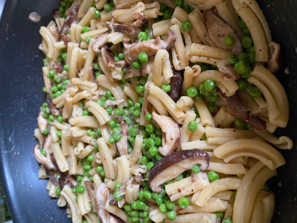 Finished Pasta with Shiitake Mushrooms & Peas in a Light Cream Sauce in the skillet.