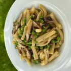 Finished Pasta with Shiitake Mushrooms & Peas in a Light Cream Sauce in a white bowl, photographed outside.