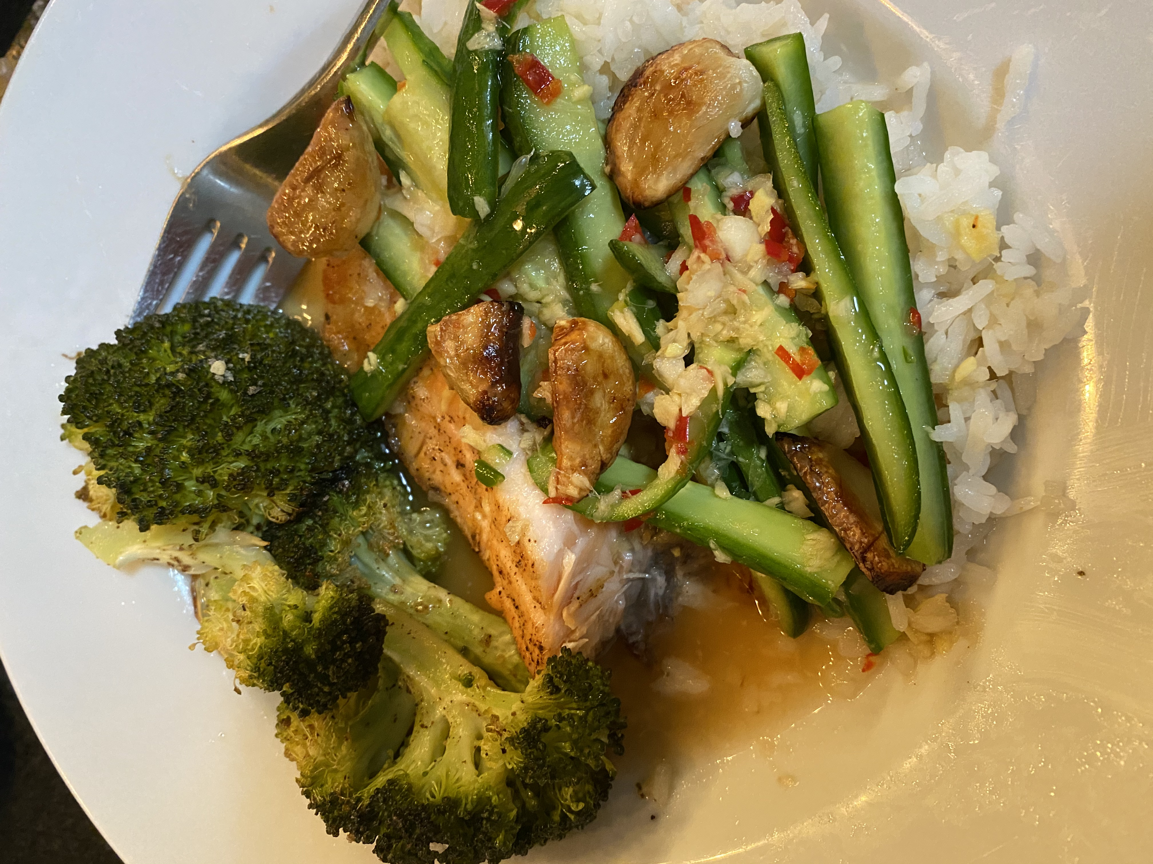 Half-eaten Salmon Rice Bowl with Ginger-Lime Sauce with a side of broccoli.