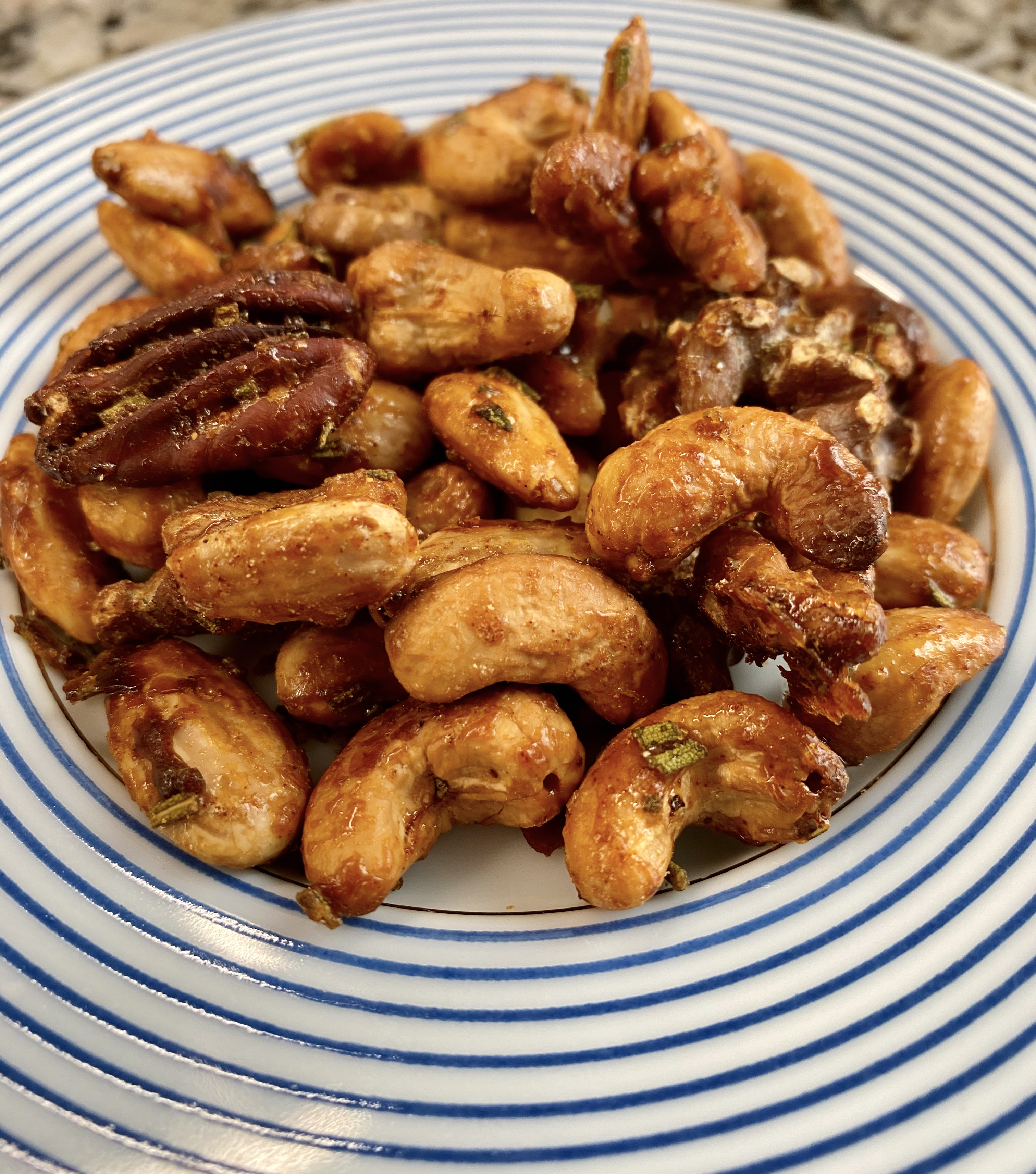 Spicy Maple Glazed Nuts are not too sweet, not too spicy, on a blue rimmed plate.