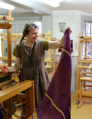 Becky hands out blankets, fresh off the loom