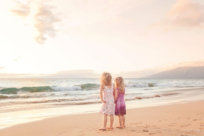 Sisters holding hands on the beach in Maui