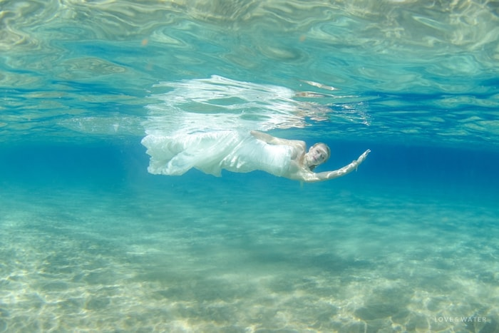 Bride swimming underwater Maui