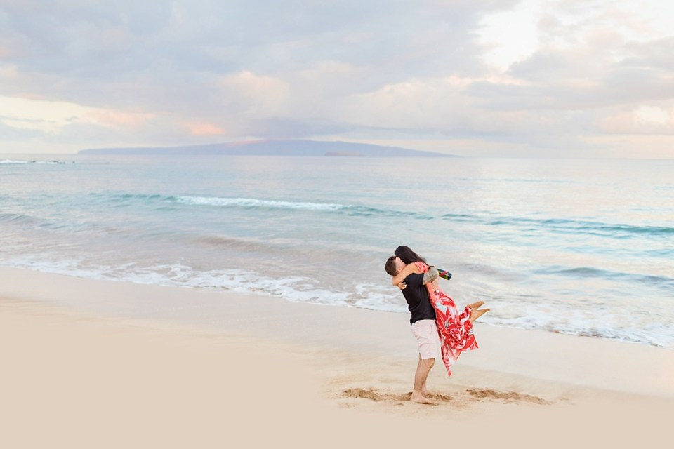 A man embraces and picks up his new fiance at an engagement session in Maui after she says yes to his beach proposal.